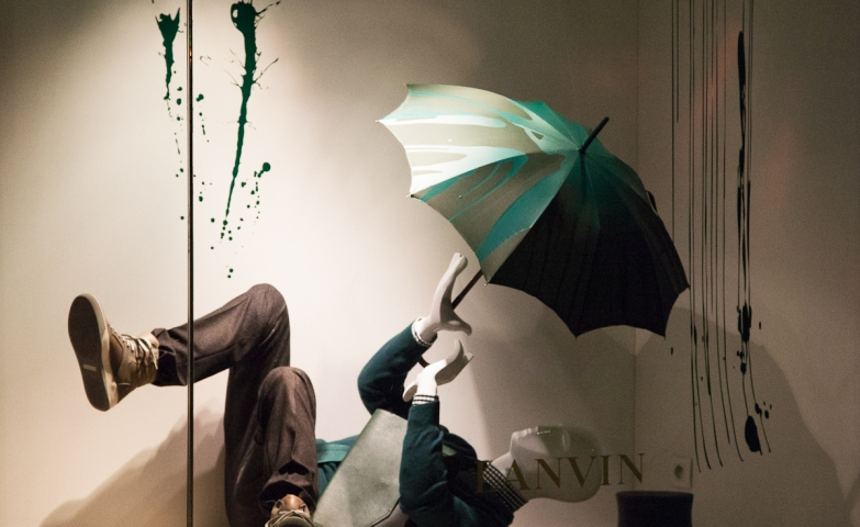 Designed in a funny way, the Lanvin window display is marking the autumn with some splashed paint signifying the raindrops and a fallen mannequin which holds an umbrella.