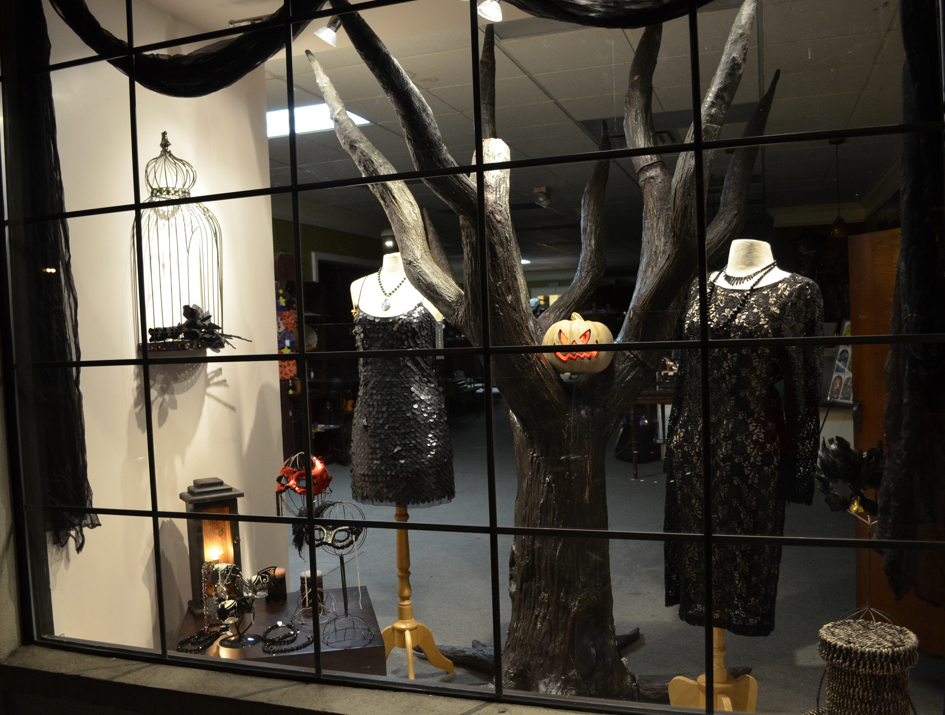 In the Oakmont Halloween window display, the scariest atmosphere is given by the big tree placed between the black clothes surrounded by a black curtain.
