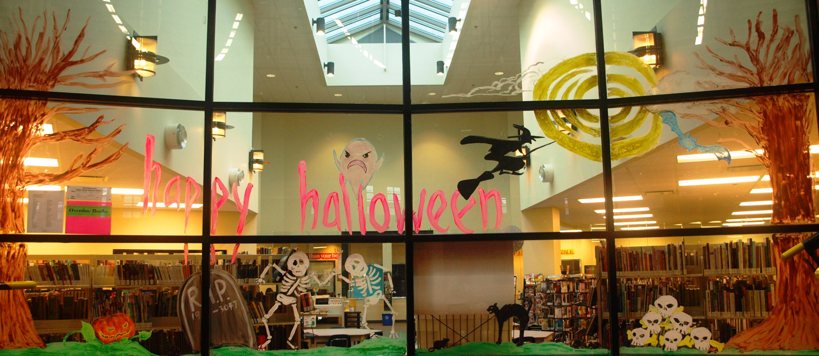 A painted window display with Halloween elements like angry ghosts, skulls and witches.