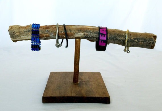 For a creative jewelry bracelet holder only needed glue, stain and wood. This one has a natural branch bar.