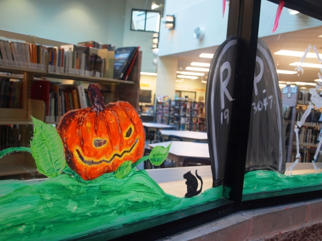 This library decorated the window display for Halloween with a painted pumpkin, a crypt and a black mouse.