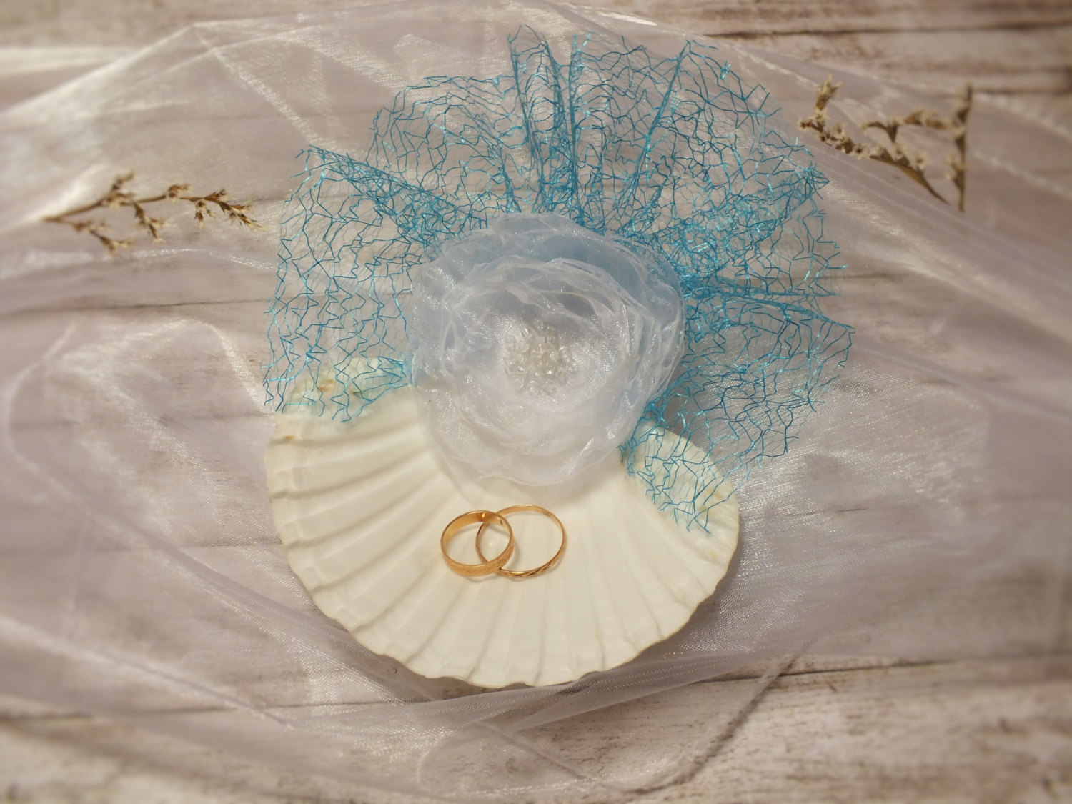 A creative jewelry ring holder for a wedding, made from natural seashell and decorated with an organza flower.