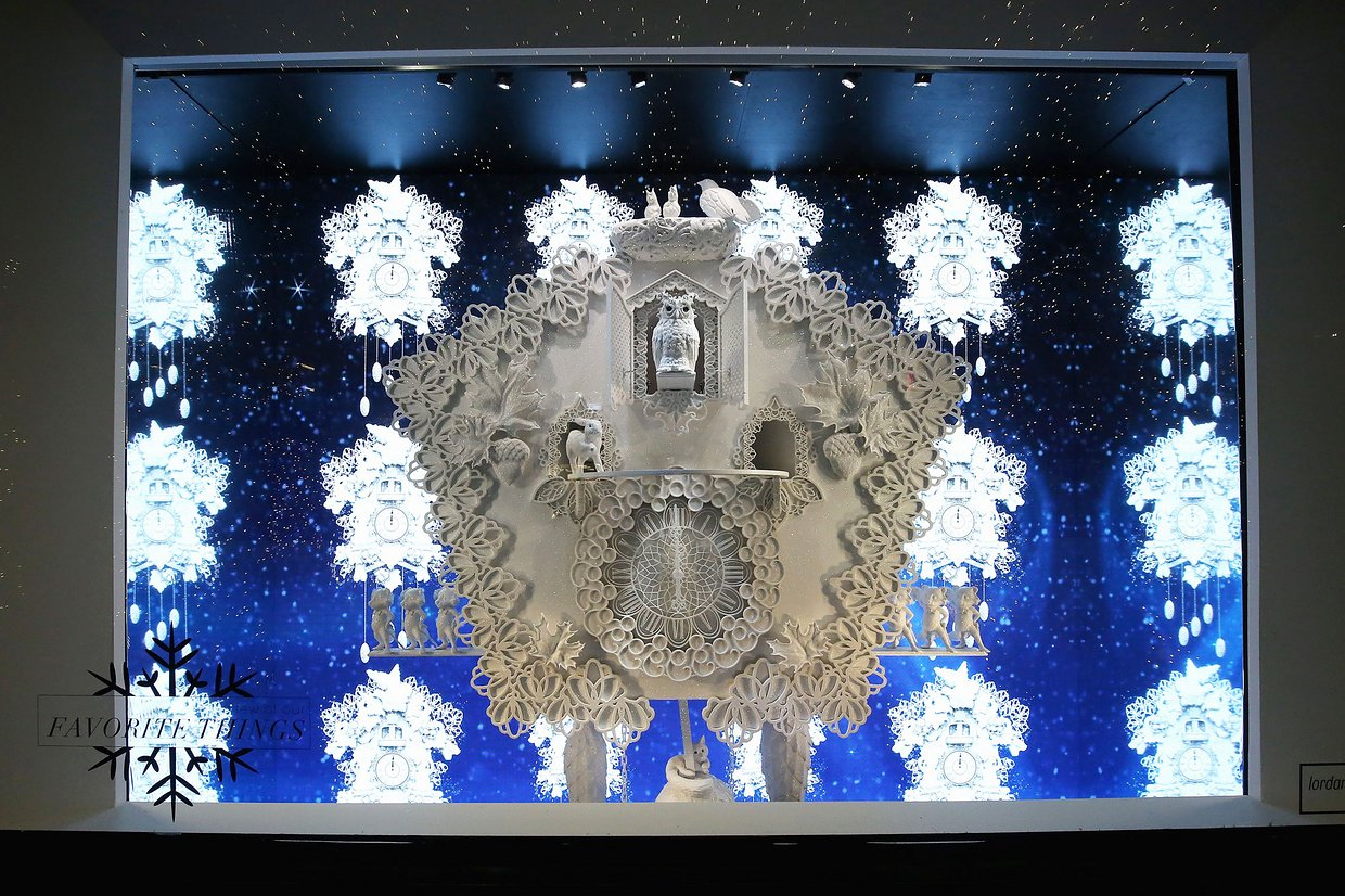 A window display with all white on a blue canvas, a clock and the owl which announce that is time for winter to take the role seriously.