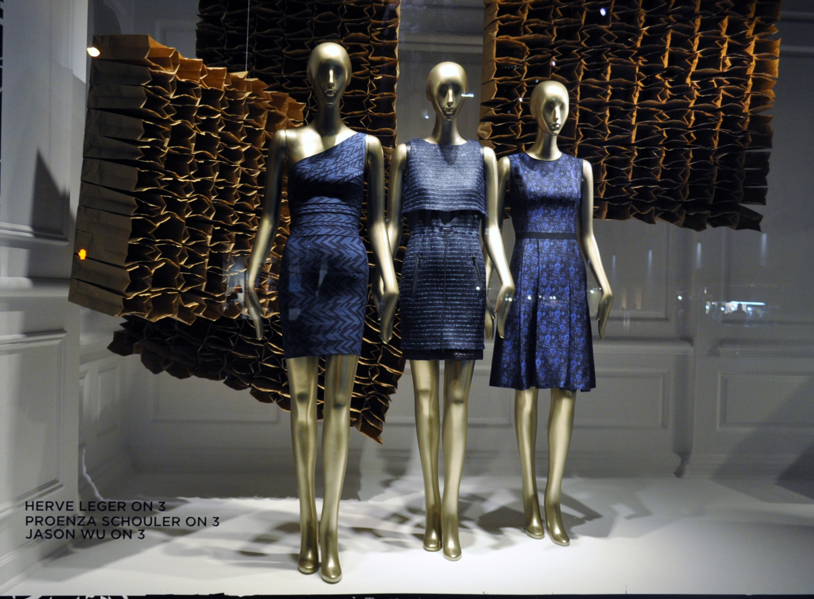 This window display from New York is decorated with something that looks like opened up cartoon boxes and three mannequins dressed in blue.