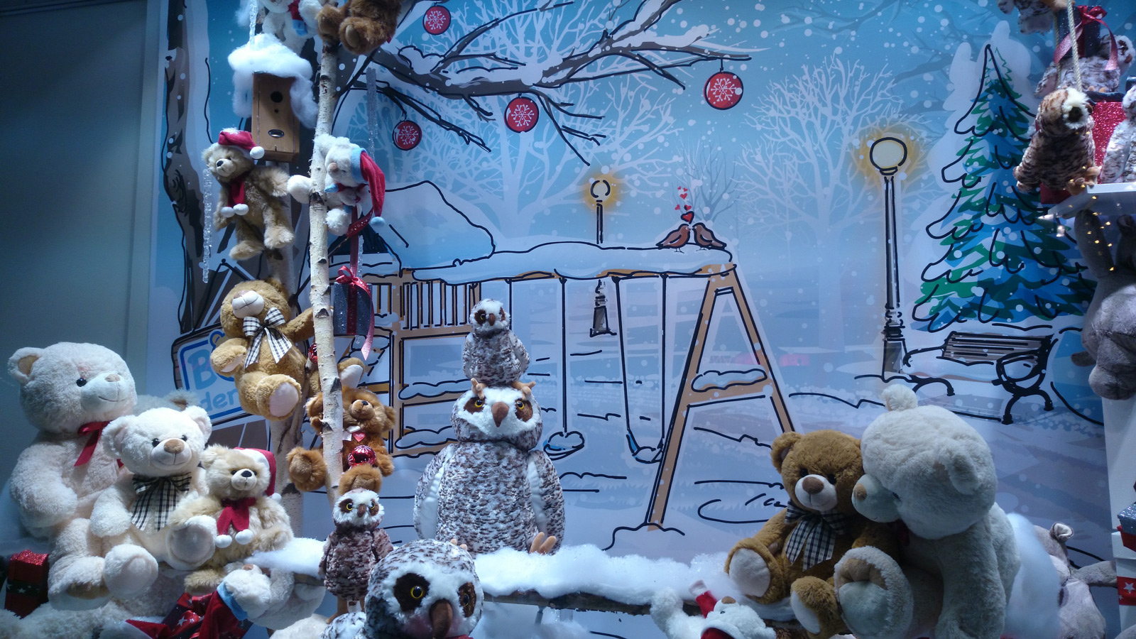Friendly window display with plush bears and plush owls, and a wall painted with a winter theme.