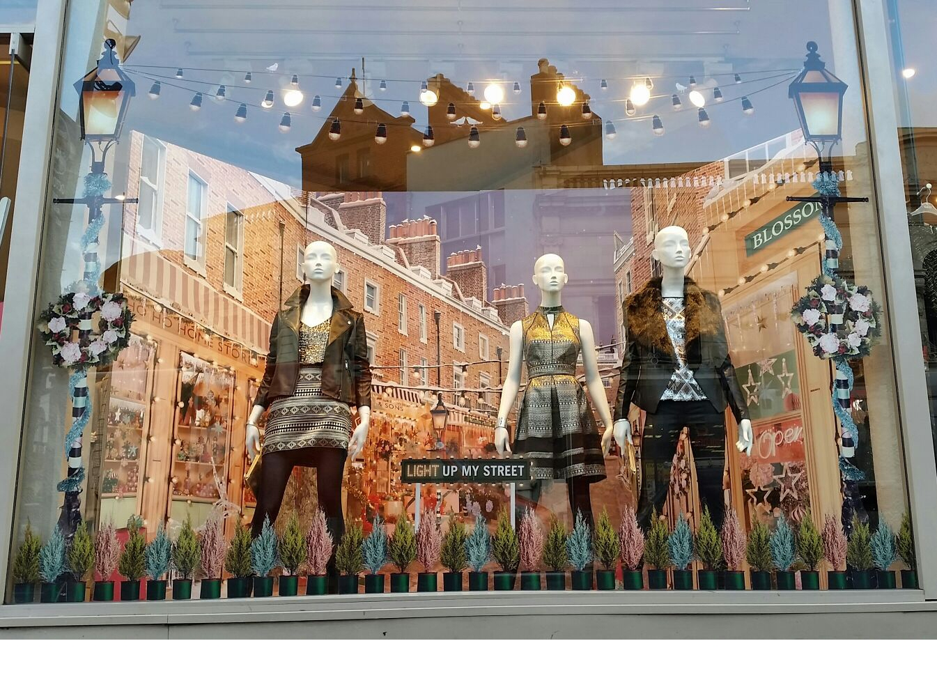 In this autumn window display, Oasis scene is about pine trees and mannequins dressed in jackets.