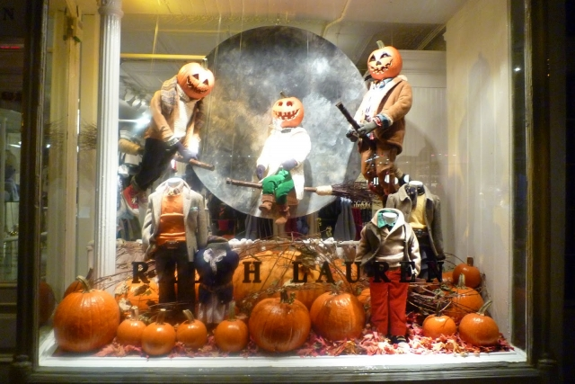 Ralph Lauren has a Halloween window display with a moon in the background and flying pumpkins on broomsticks.