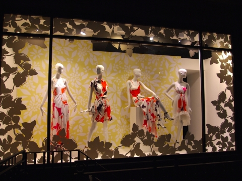 A summer window display decorated with a yellow background and four mannequins dressed in red and white pattern dresses.