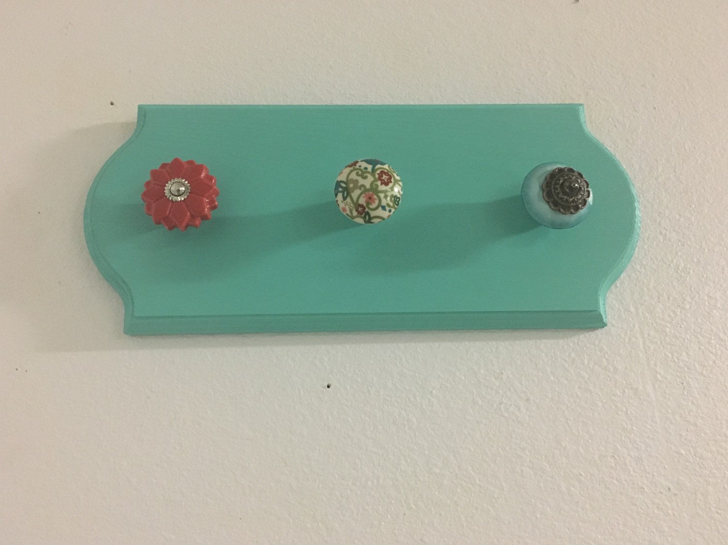 Gorgeous plaque painted in mint aqua color, and three knobs added in a creative way to make together a jewelry necklace holder.