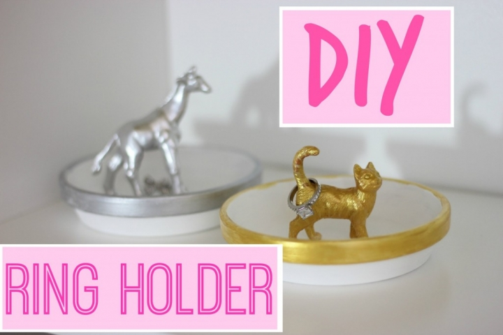 This looks like a creative pottery plate for jewelry, with gold paint on the border, and a little cat with the tail up, also from pottery, good as a ring holder.