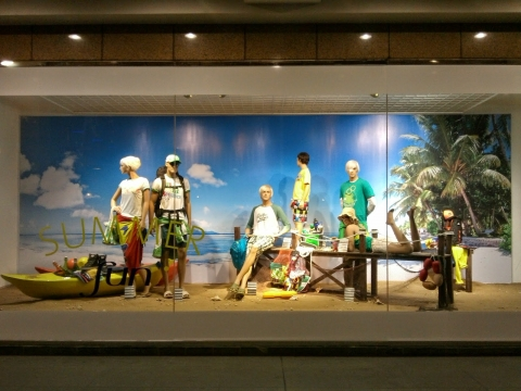 """Window display ready for summer, prepared with sand, mannequins in flip flops a tag with """"summer fun""""."""