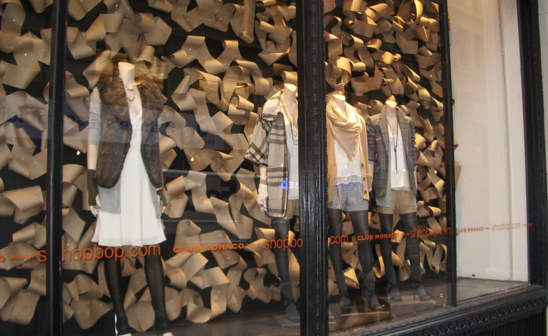 Paper curls in the background, for a warm design, added to the neutral style of clothes for the autumn window display.