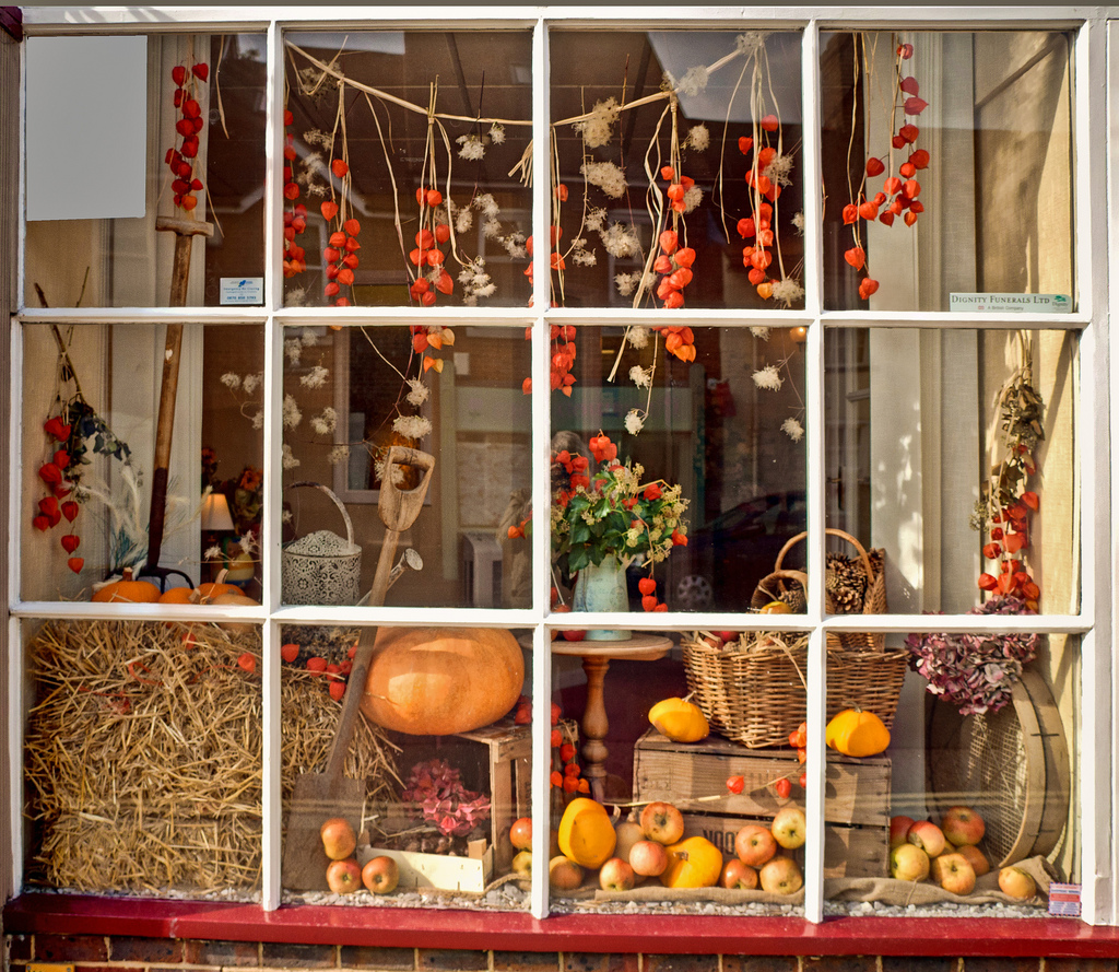 Square window store designed for autumn with pumpkin and apple for the display.