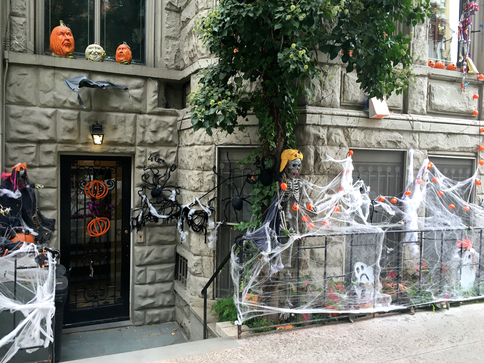 A decoration for a Halloween window display with spiderweb all over the front windows, different types of pumpkins, sculpted in different ways, and little pumpkins placed on the spiderweb.