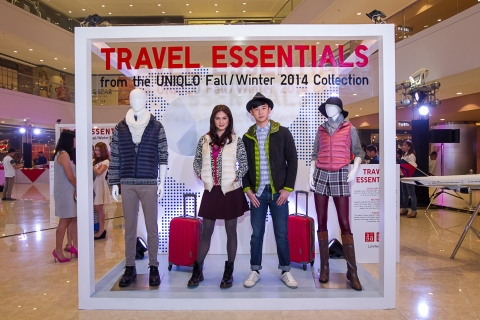 Unique kind of decorating an autumn window display with real people among mannequins, dressed in essential clothes for travel.