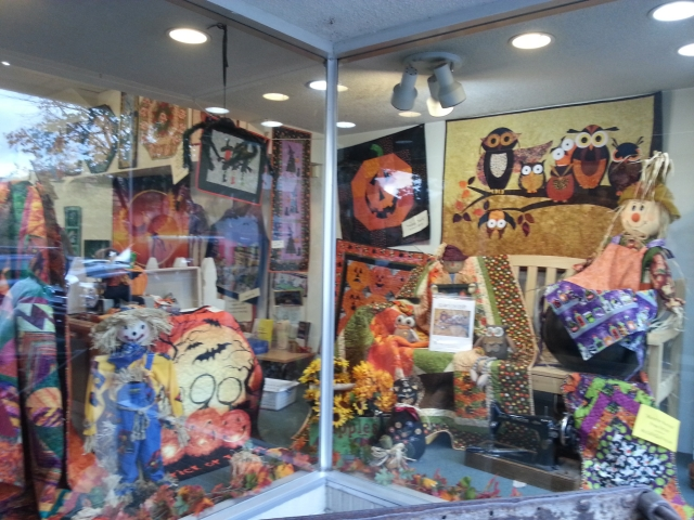 Lively looking shelves of Halloween fabric with decorative artifacts in this window display.