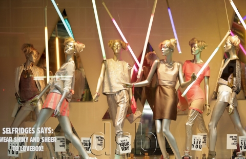 Selfridges decorated its summer window display with shiny clothes and some neons in the background and a cute message.