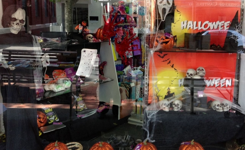 A skeleton dressed in a black long dress, glitter pumpkins, all this for a Halloween window display.