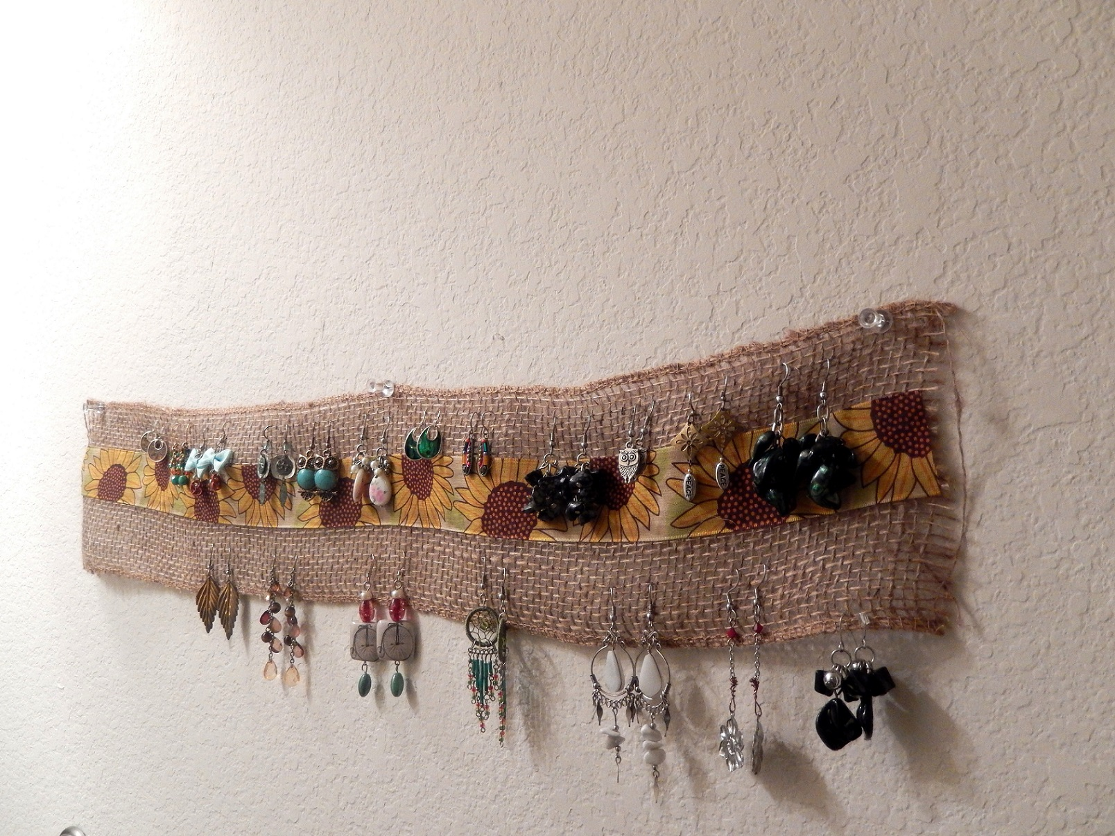 A creative jewelry earring holder can be simply made out of a piece of rough material, and then added in the middle a strip from soft fabric with any pattern you want.