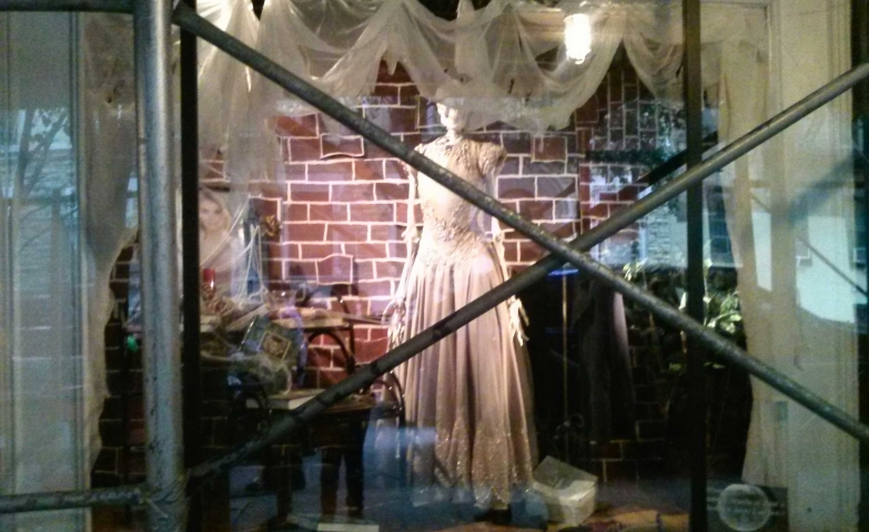 A Halloween window display that highlights a skeleton bride surrounded by white curtains.