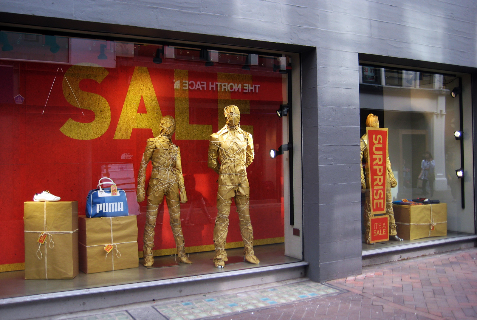 Puma has sales and a wrapped box plus a wrapped mannequin for autumn window display.