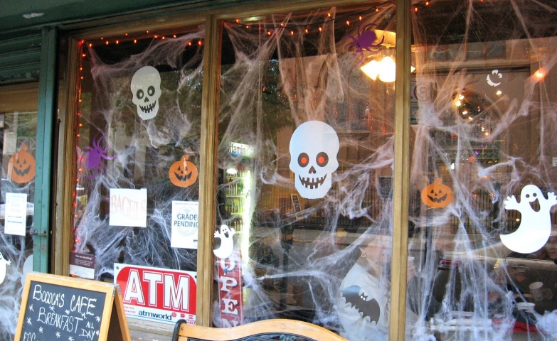 A window display prepared for Halloween with a lot of spiderweb, skull and spider stickers. Looking more cute than scary.