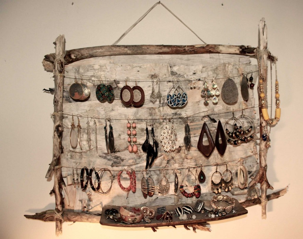This creative jewelry earring holder was built up from sticks, a wood pannel and metal strings.