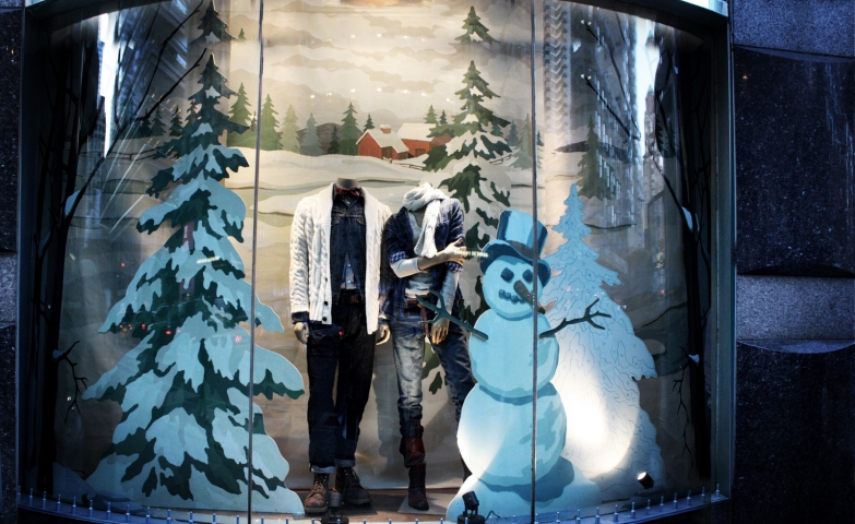 Two mannequins between a window display prepared for winter, with one lovable snowman and some fir trees covered with snow.