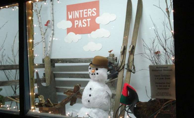 What a perfect scene for a winter display: a snowman, a sleigh and a pair of ski.