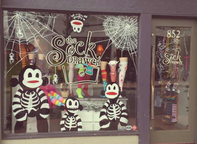 A Halloween window display that features some spooky skeleton sock monkeys by a couple scary spider friends.