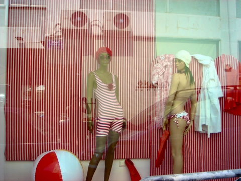A summer window display for old fashion lovers with old fashion swimsuits with red and white stripes.