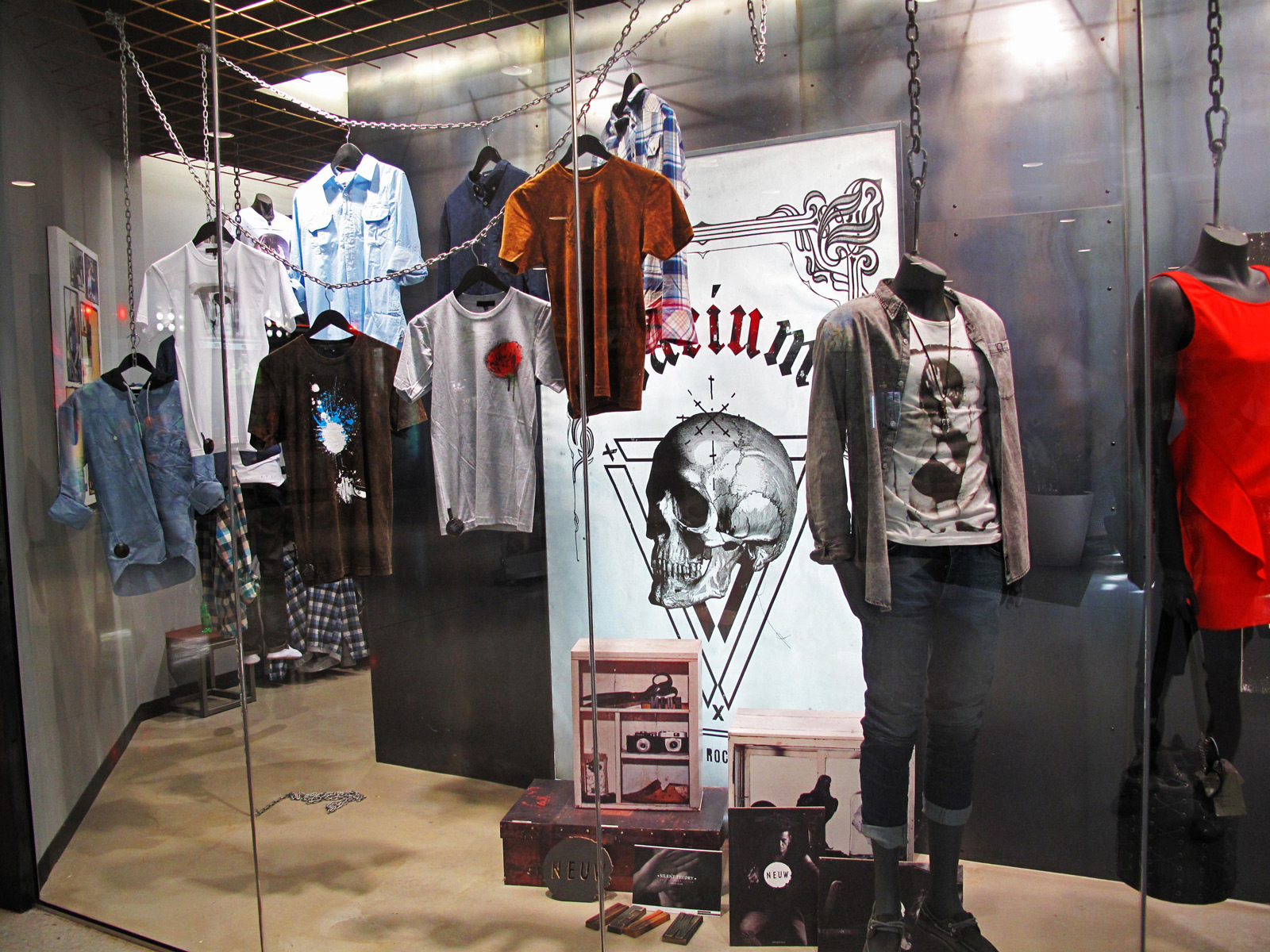 An autumn window display decorated with hanging t-shirts in chains and a skull drawn on the background.