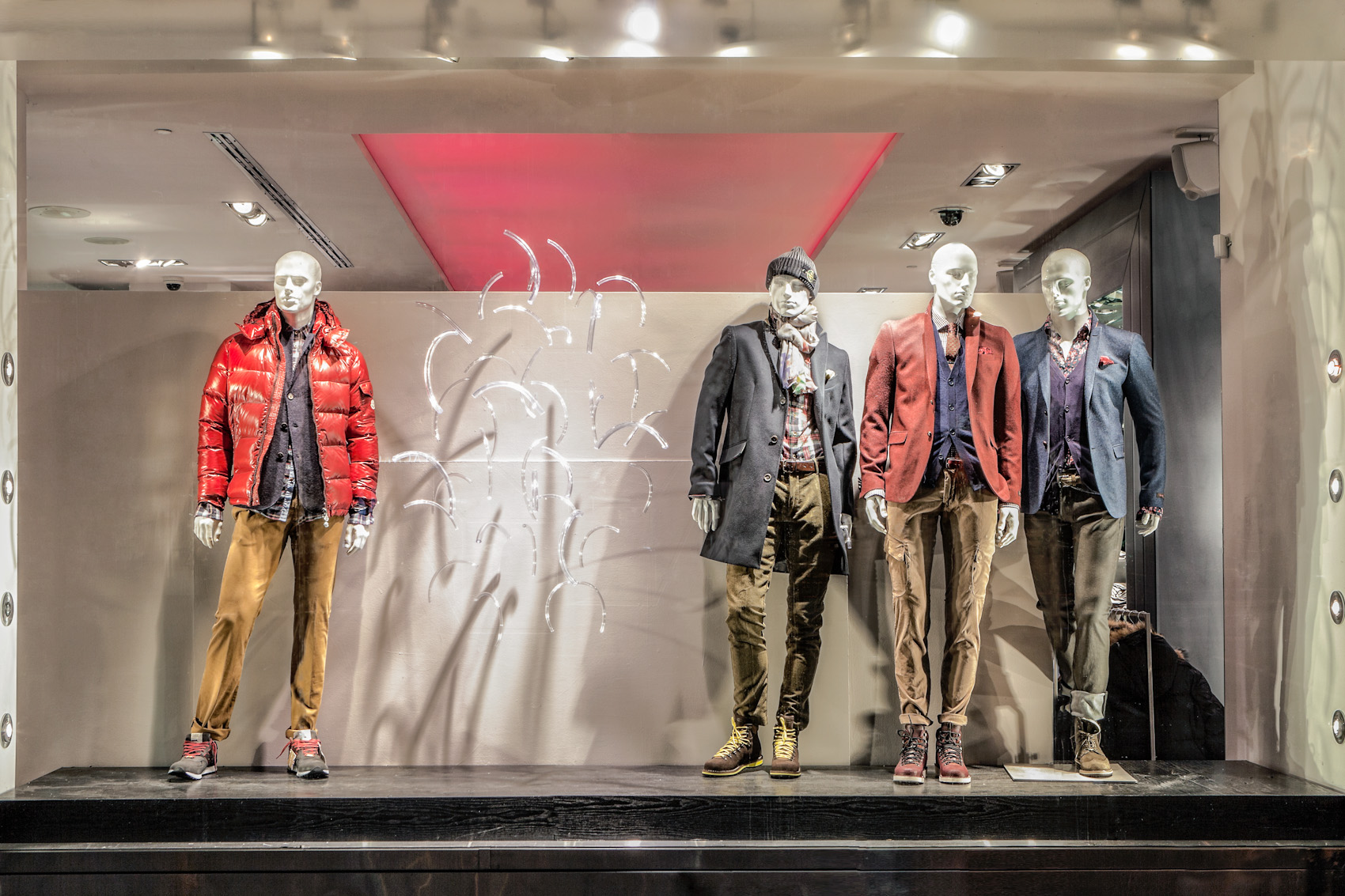 Thick clothes in autumnal colors and gray background are composing one autumn window display.
