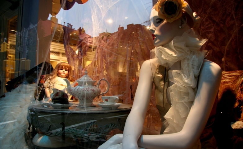 A tea party for Halloween with a pale mannequin and a creepy doll standing between a lot of spider webs, placed in the window display.