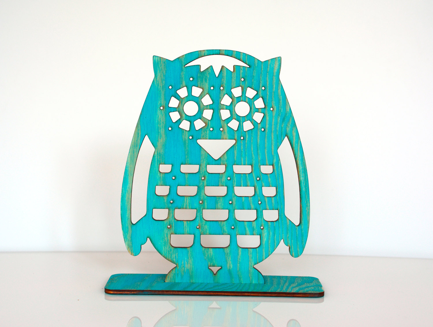 Specially designed as a jewelry earring holder, in a creative way, with a shape of an owl, made of wood and painted in turquoise.