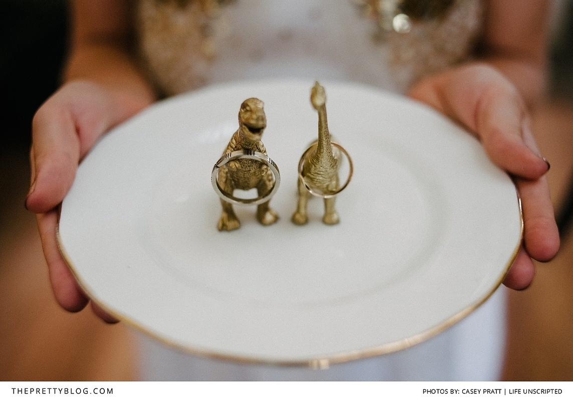 A creative jewelry ring holder for a wedding, made by two golden little dinosaurs.
