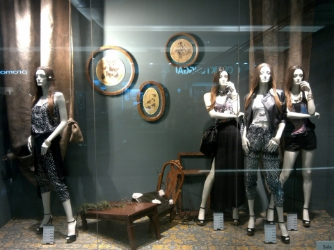 Autumn is happening in Stradivarius window display, showing us a group of mannequins standing in a place that reveals a deserted house with broken table and a broken chair, looking very old.