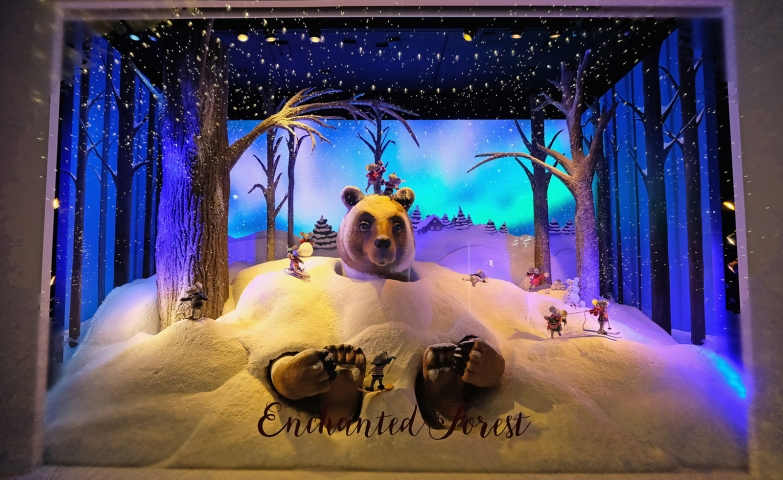 A bear sneaked in snow, in a forest scene, this is a cute winter window display.