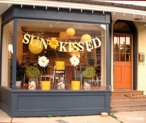 A sun-kissed place decorated with flowers and yellow details for summer window display.