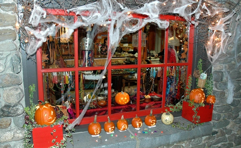 A traditional red Halloween window display decorated with carved pumpkins and spiderweb.