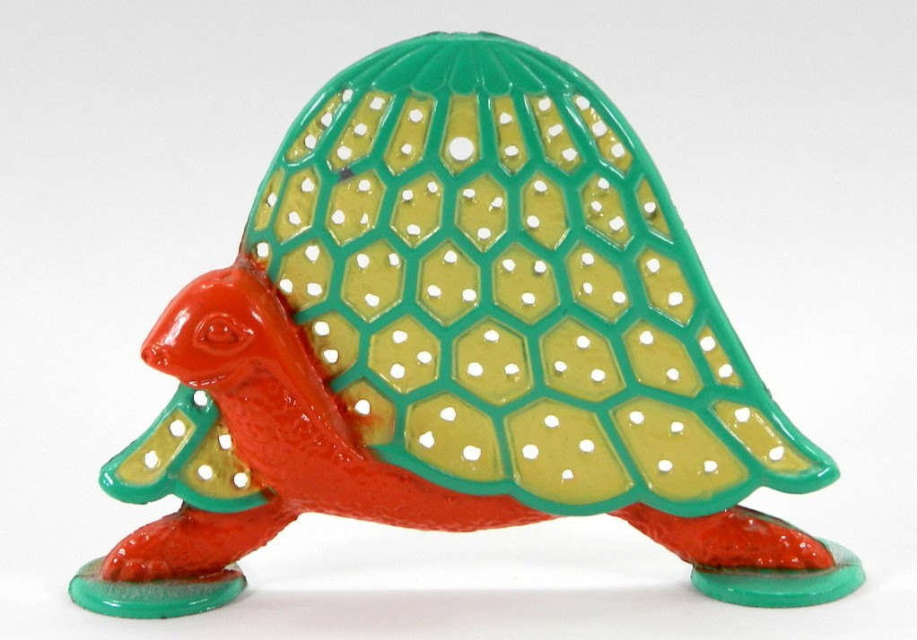 Vintage and creative, this turtle made from metal is in a very good condition for its age and a good jewelry earring holder. It's painted in green and orange.