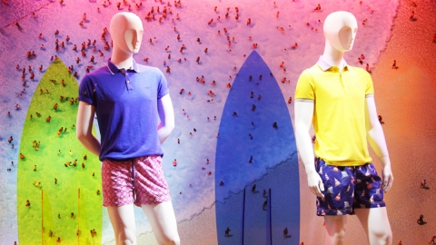 A window display that represents summer at its best with surfboards and people enjoying the water.