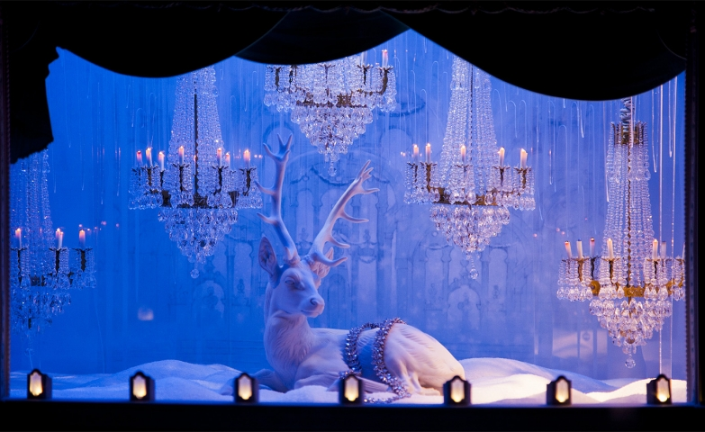 The hung chandeliers, the white reindeer and the color on the background make everything in the winter window display for Tiffany looking royal.