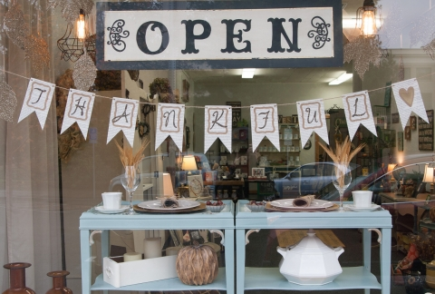 A window display which wants to help you to proper decorate your autumn buffet, with a thankful message and a gold painted heart.