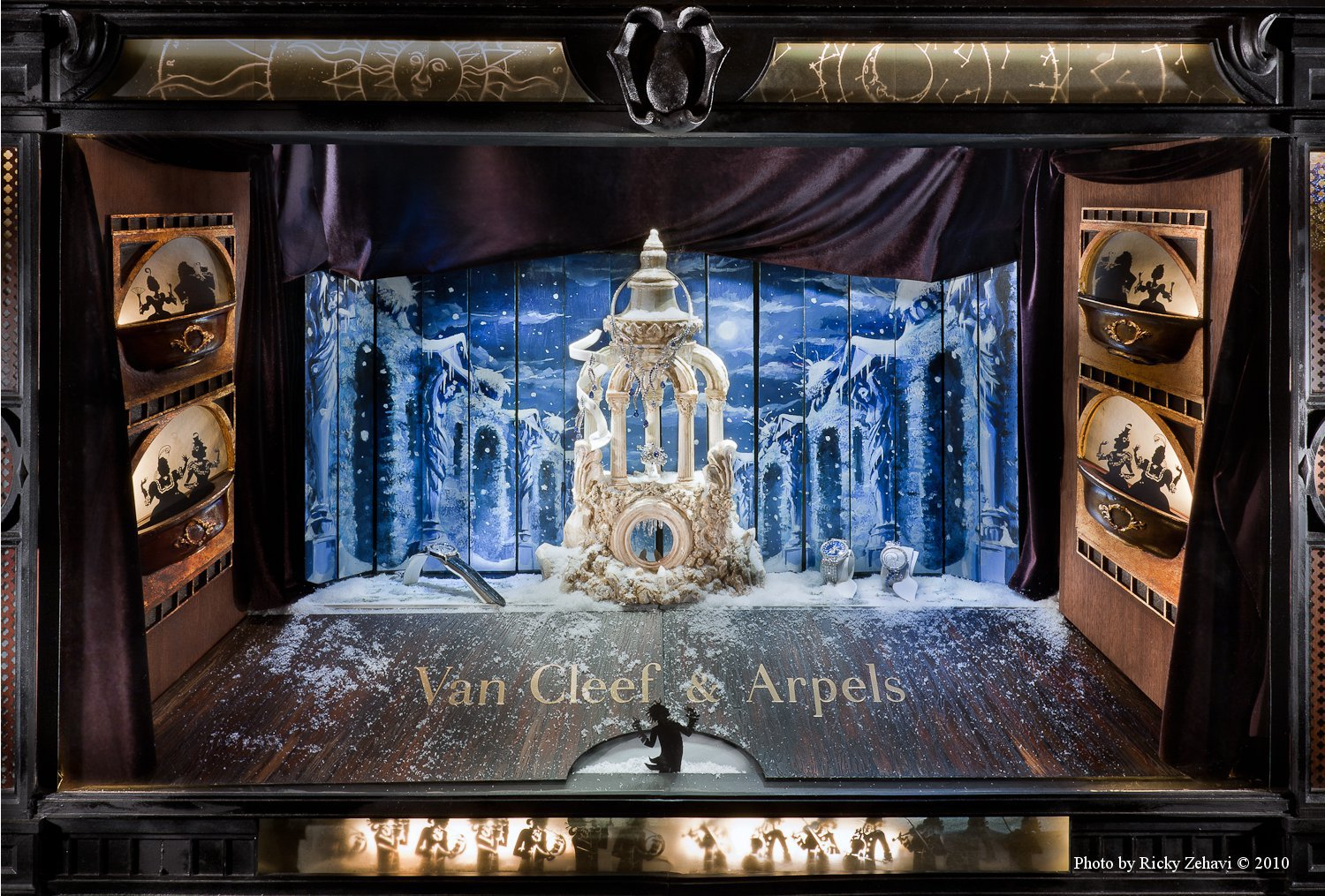 Van Cliff & Arpels has a special winter window display which is looking like a scene from the theatre with a picture in the background showing iced nature.