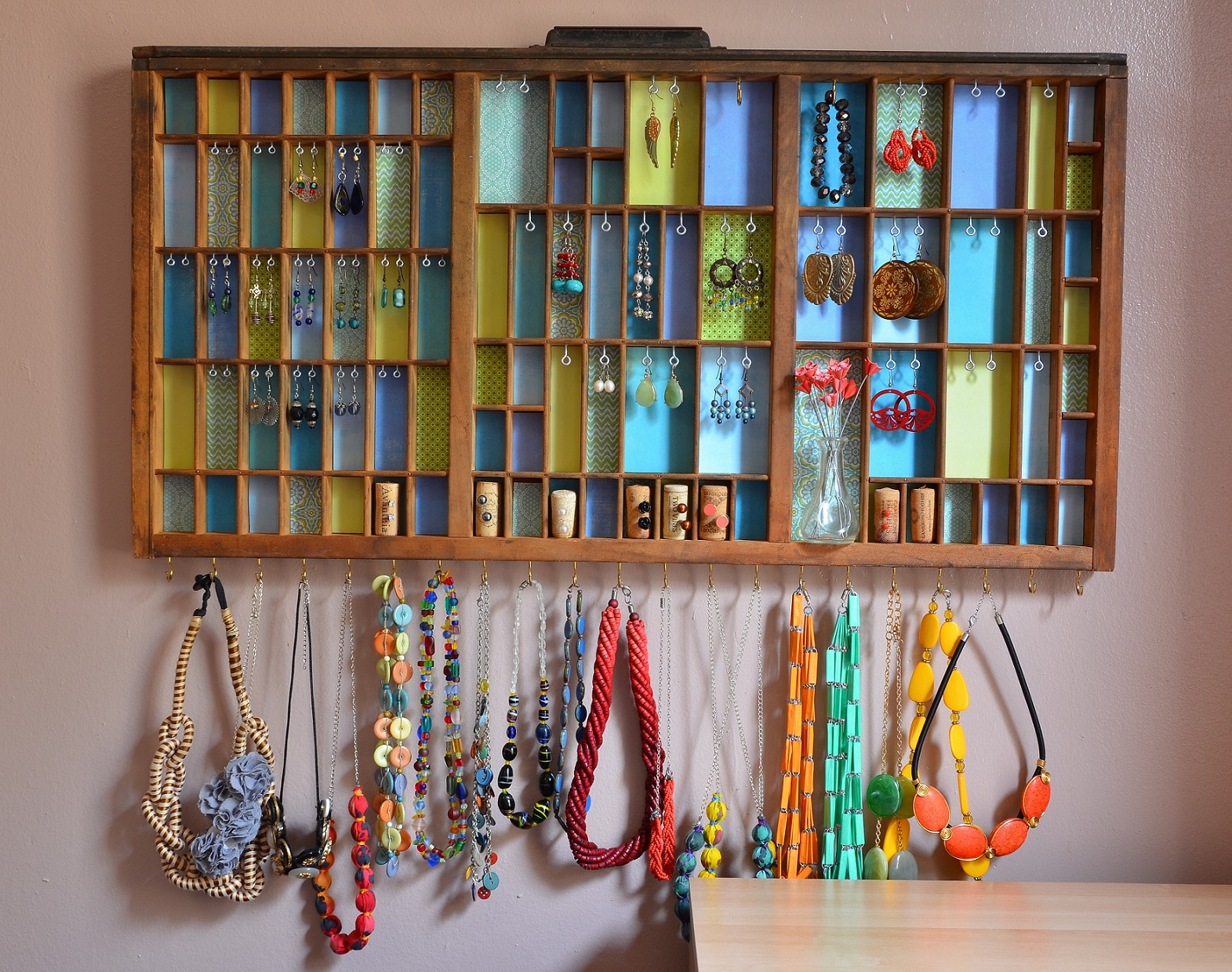 In the bottom part of this colored wood locker, were pinned some hooks, and a creative way to hold your jewelry necklace was taken place.