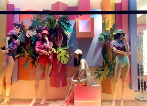 Even mannequins from this window display are thinking about summer with such a tropical color background.