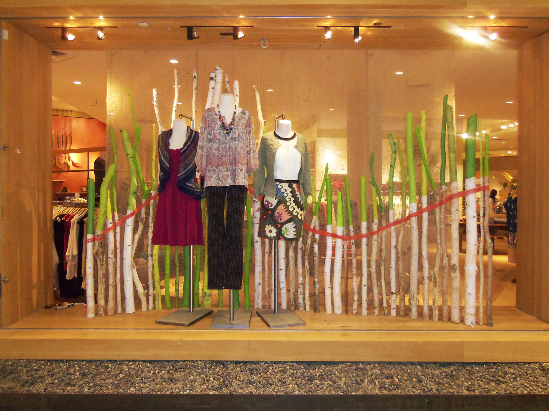 Anthropologie autumn window display is defined by a few trunks split in two colors, green and white, which could be the point of plants changing by the season.