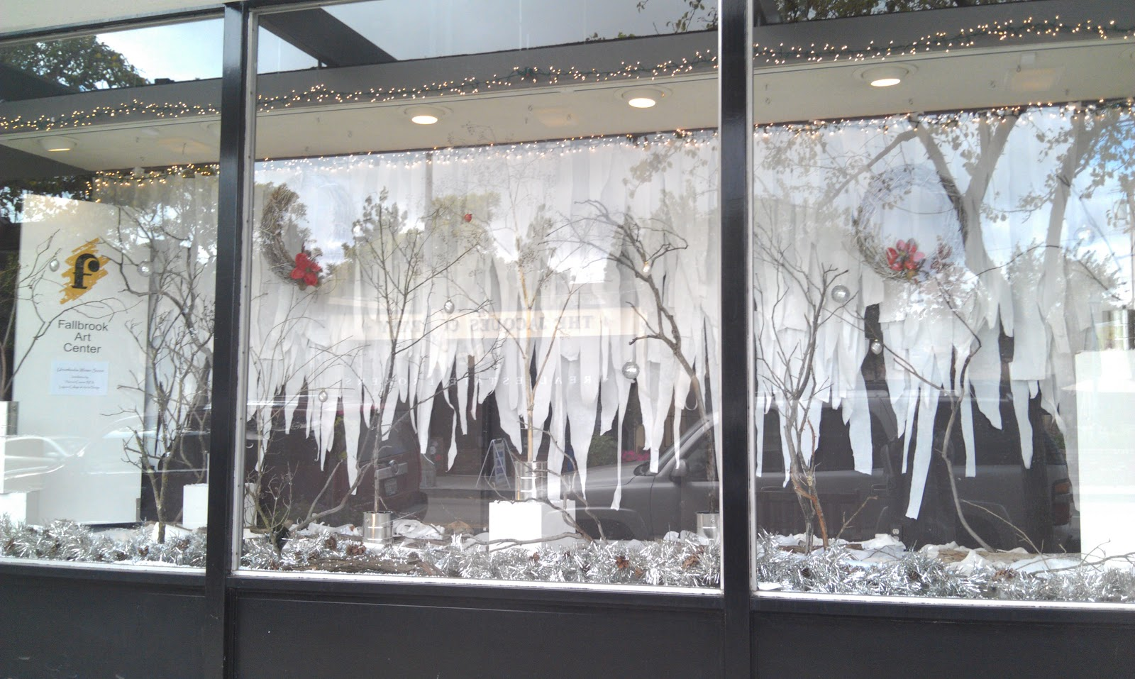For this winter window display, we have in the back a cut white curtain into strips and fallen trees branches cemented into paint buckets.