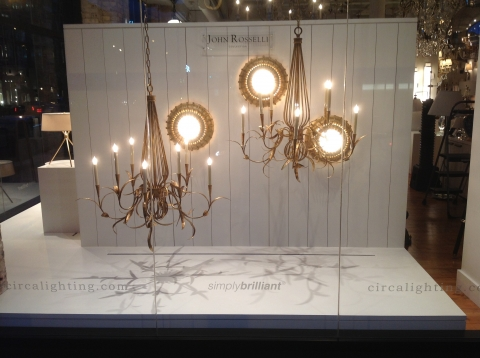 John Rosselli summer window display has an elegant air with those three light chandeliers and the white wall.